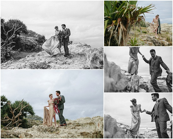 Groom helps bride down the rocks onto the beach