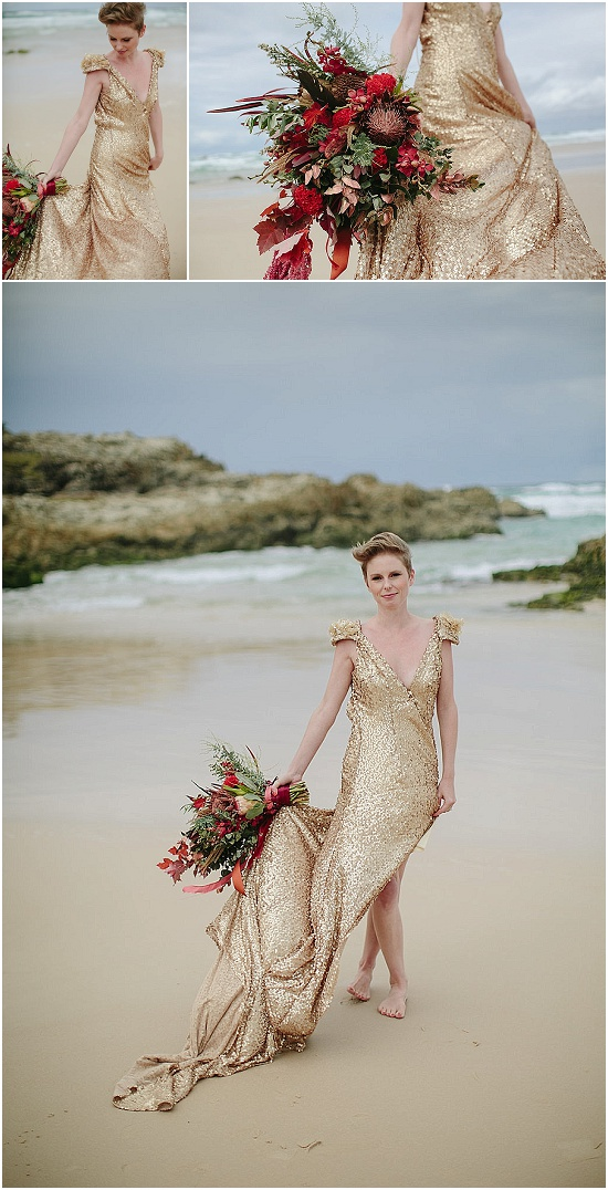 Bride poses in gold sequined gown with an oversized deep red bouquet