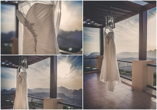 the wedding dress hangs in the balcony overlooking the mountain ranges of Petra at sunset
