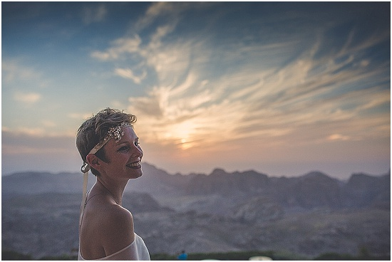 the bride wears an elegant white wedding dress at sunset overlooking the mountain ranges of Petra