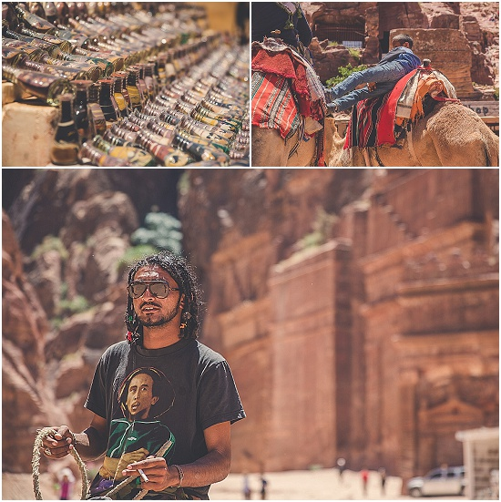 A boy leans between two camles and a man wearing a Bob Marley t-shirt rides a camel in front of Petra, Jordan