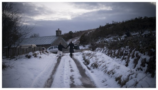 A couple stroll down a snowy road at a wedding in Scotland