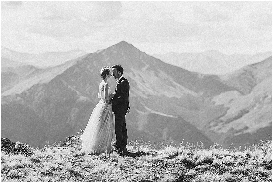 a couple stand on the edge of a mountain at a wedding in Queenstown New Zealand