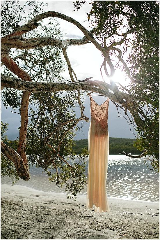 a wedding dress hangs in a breeze in a tree