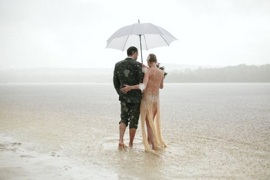 newly weds wade into lake in rain storm after a wedding on stradbroke island