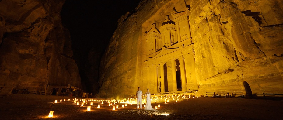 Lisa and Alex stand in hundreds of candles in front of The treasury after their wedding in Petra