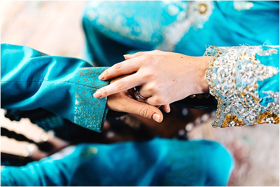 Bridal couple hold hands wearing traditional Malaysian wedding attire