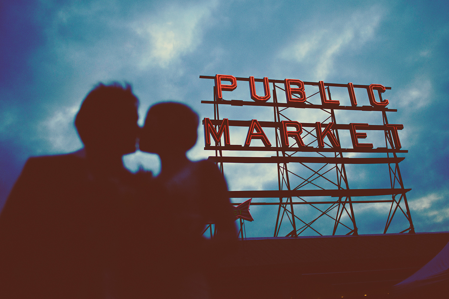 A silhouette of a bride and groom in front of the Pike Place market sign at their wedding in Washington, Seattle